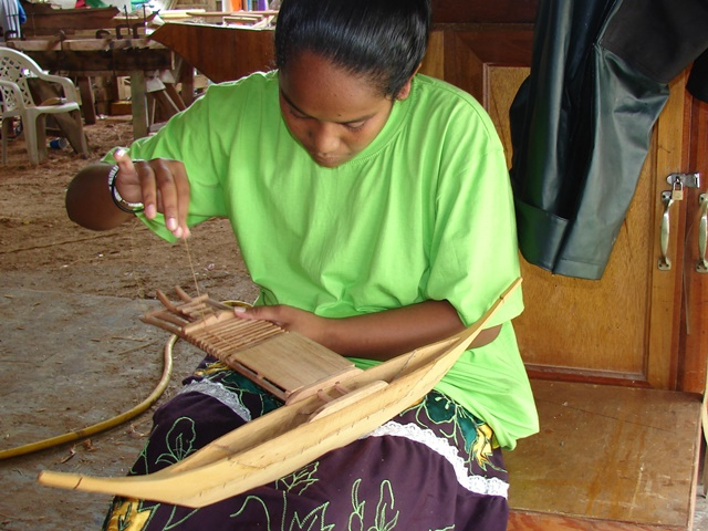 A trainee lashes the platform between the outrigger and the hull on a model canoe.