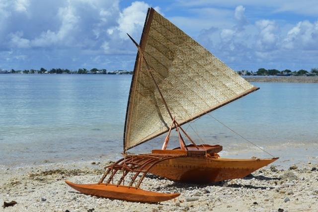 A model canoe, measuring three feet, made by WAM trainees sits on the beach next to the Canoe House.