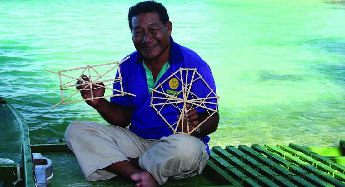 Master navigator Captain Joel Korent holds stick charts, which are key to training of novice navigators.