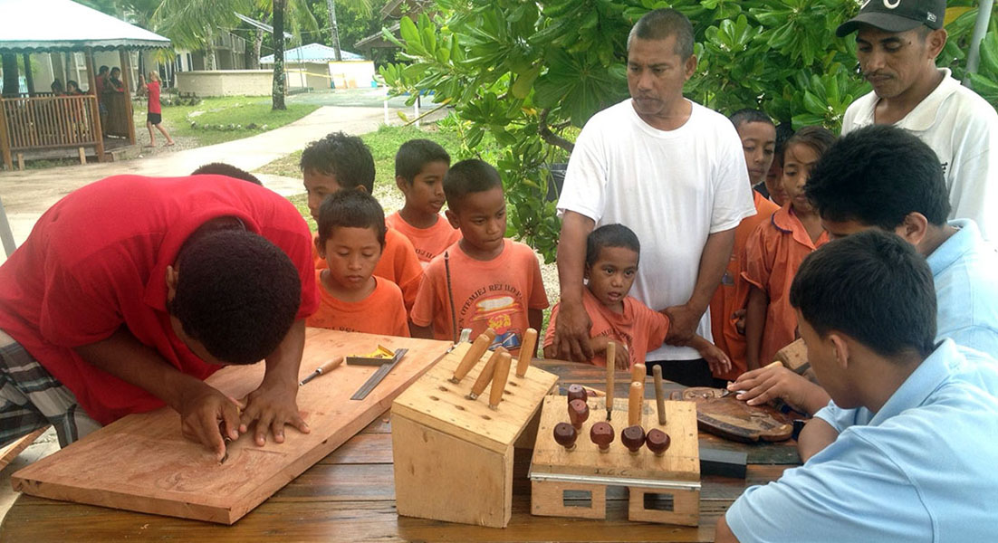 Trainees show off their newly-learned carving skills to a group of visiting school children.