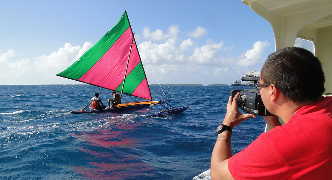Fiji photographer from the South Pacific Forum shoots a canoe underway.