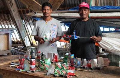 WAM's Linton Baso and Binton Daniel work on the yacht club beer can boats. Photo: Laura Masterson.