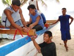 Young men of Ailuk work on the refit of the canoe in 2013.