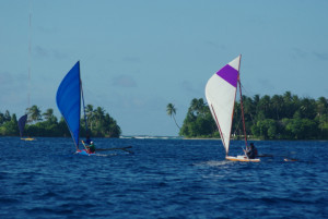 hree canoes race to the rounding mark in the Majuro Day 2015 Canoe Race.